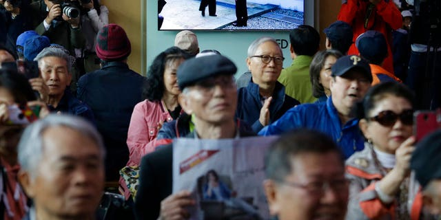 In this April 27, 2018 photo, People watch a TV screen showing the live broadcast of South Korean President Moon Jae-in, top right, meets with North Korean leader Kim Jong Un at the border village of Panmunjom during a news program at the Seoul Railway Station in Seoul, South Korea