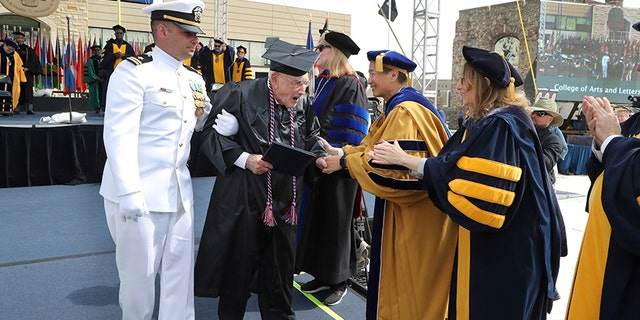 Barger, assisted by Ghanbari, greeted school officials at the University of Toledo graduation on Saturday.