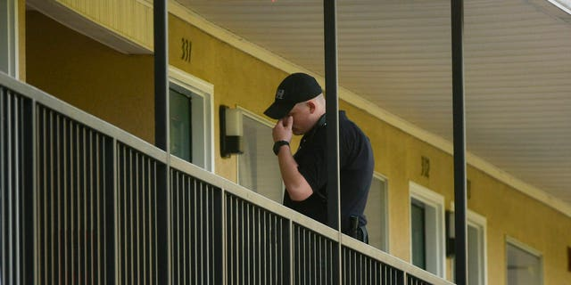 A DeKalb County law enforcement officer stands outside a guest room at the United Inn and Suites Hotel Saturday.