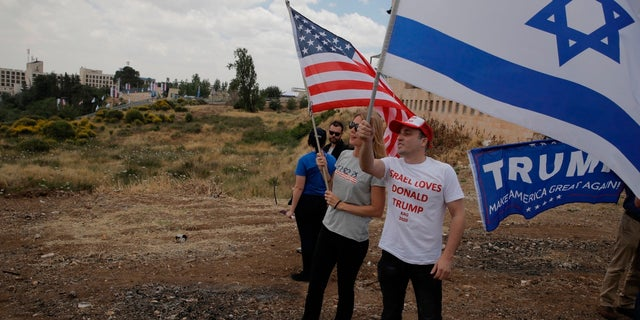 Israelis hold American and Israeli flags with the new U.S. embassy in the background in Jerusalem, Monday, May 14, 2018. Israel prepared for the festive inauguration of a new U.S. Embassy in contested Jerusalem.