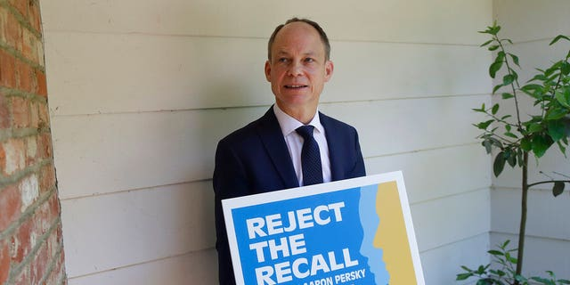 """Aaron Persky holds a """"Reject the Recall"""" placard in Los Altos Hills, Calif., May 15, 2018.聽(Associated Press)"""