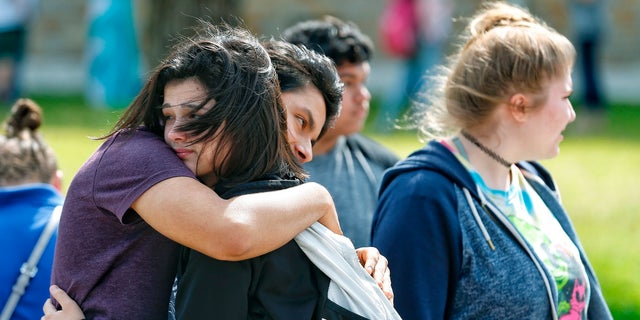 Santa Fe High School freshman Caitlyn Girouard, center, hugs her friend outside the Alamo Gym where students and parents wait to reunite following a shooting at Santa Fe High School on Friday.