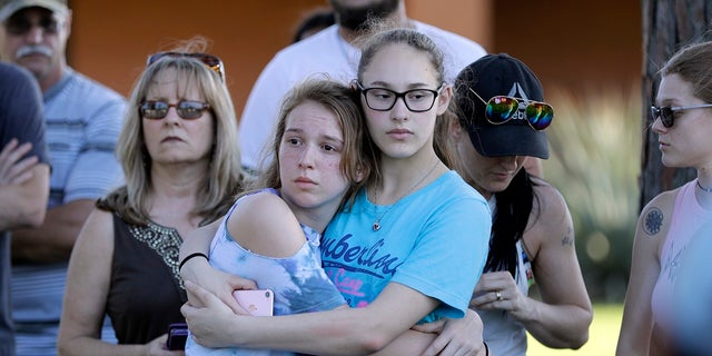 Mourners wait for the start of a prayer vigil following a deadly shooting at Santa Fe High School in Santa Fe, Texas, on Friday, May 18, 2018.