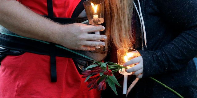 Santa Fe High School freshman Kylie Trochesset, right, is comforted by her father, Jared, during a prayer vigil following a shooting at Santa Fe High School in Santa Fe, Texas on Friday.