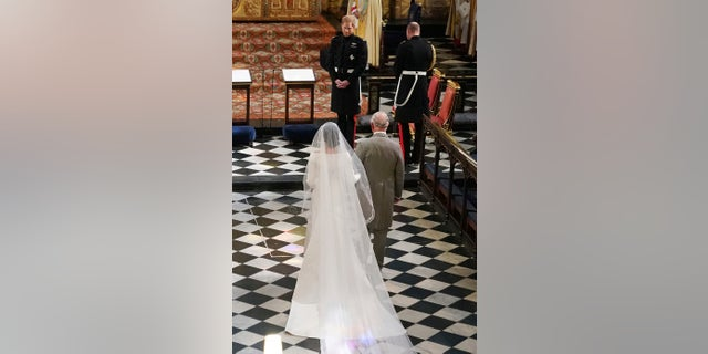 Britain's Prince Harry looks at his bride, Meghan Markle, as she arrives accompanied by Prince Charles during their wedding ceremony at St. George's Chapel in Windsor Castle in Windsor, near London, England on Saturday.