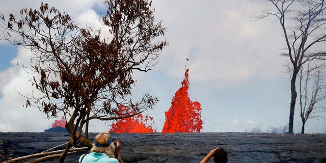 People take pictures as fissures spew lava in the Leilani Estates subdivision near Pahoa, Hawaii.
