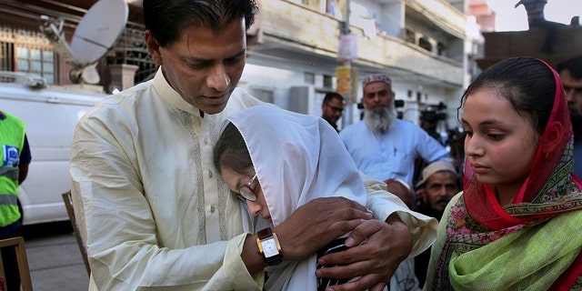 Abdul Aziz Sheikh, father of Sabika Sheikh, the Pakistani exchange student killed in a mass shooting at a high school in Texas, comforts Sabika's friends outside his home prior to her funeral prayer in Karachi, Pakistan.