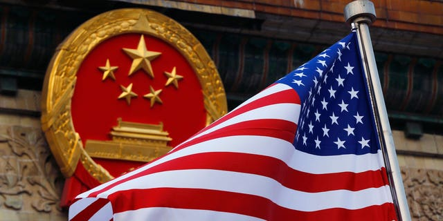 An American flag is flown next to the Chinese national emblem during a welcome ceremony for visiting U.S. President Donald Trump outside the Great Hall of the People in Beijing.