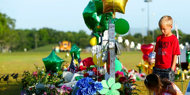 Two children look at a memorial for the Santa Fe High School shooting victims outside the school Wednesday, May 23, 2018, in Santa Fe, Texas.
