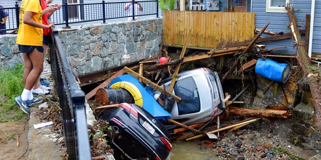 Residents gather by a bridge to look at cars left crumpled in one of the tributaries of the Patapsco River that burst its banks as it channeled through historic Main Street in Ellicott City.