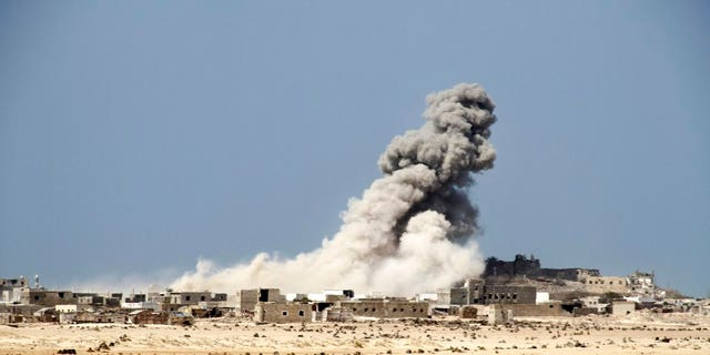 An explosion raises a cloud as coalition-backed fighters advance on the Red Sea port town of Mocha in Yemen in this Jan. 11, 2017, photo, part of a campaign that eventually recaptured the town from Shiite Houthi rebels.