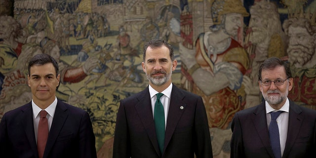 Spain's socialist leader Pedro Sanchez, left, poses with King Felipe VI, center and former Prime Minister Mariano Rajoy after the swearing in ceremony at the Zarzuela Palace on the outskirts of Madrid, Spain.