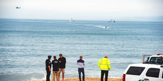 Members of the New York State park police look near the scene of a plane crash in the ocean off Indian Wells Beach in Amagansett, N.Y.