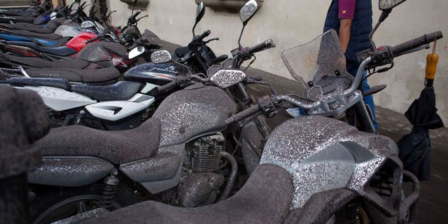 Volcanic ash covers parked motorcycles, brought by the Fuego Volcano, in Antigua Guatemala, Sunday, June 3, 2018.
