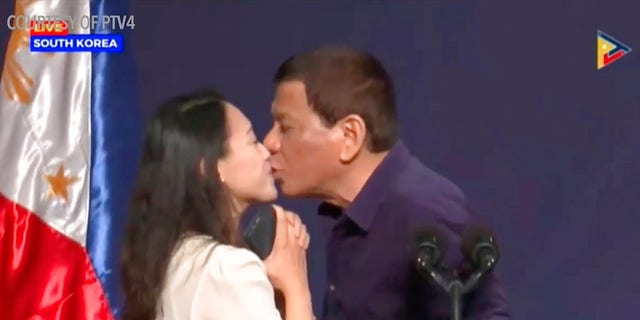 Duterte was criticized for kissing a Filipino worker at the podium.
