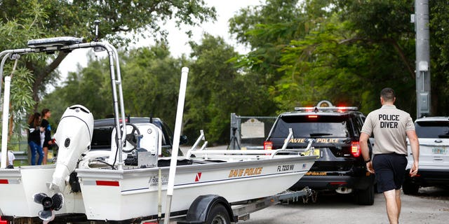 Police divers haul a boat to the entrance of Silver Lakes Rotary Nature Park after a woman was dragged into the lake by an alligator.