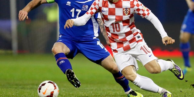 Iceland's Aron Gunnarsson, left, is challenged by Croatia's Luka Modric during their World Cup qualifying playoff in 2013.