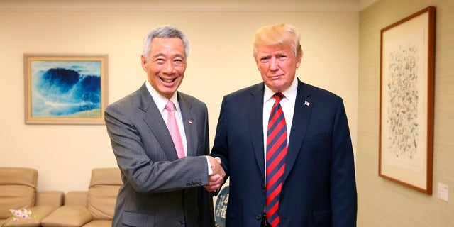 U.S. President Donald Trump, right, and Singapore Prime Minister Lee Hsien Loong, left, shake hands in Singapore, ahead of a summit with North Korean leader Kim Jong Un.