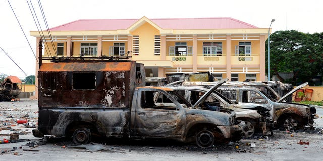 A row of charred vehicles is seen at the fire and police station in the south central province of Binh Thuan, Vietnam on Tuesday after protests on Sunday and Monday