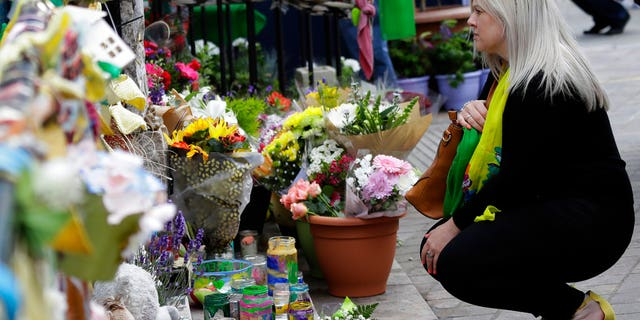A woman looks at tributes outside Notting Hill Methodist Church in support for those affected by the massive fire in Grenfell Tower in London