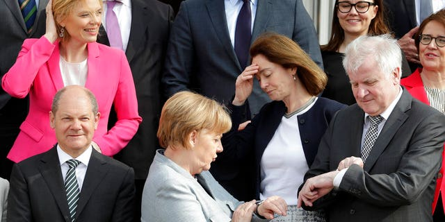 Time's up? Angela Merkel and Horst Seehofer look at their watcher while they were posing for a group photo in April