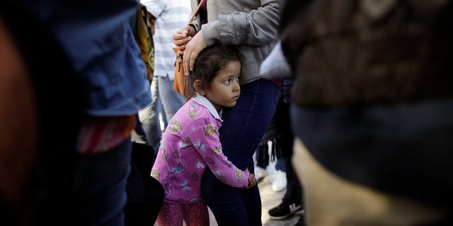Nicole Hernandez, of the Mexican state of Guerrero, holds on to her mother as they wait with other families to request political asylum in the United States, across the border in Tijuana, Mexico. The family has been waiting for about a week in this border city hoping for a chance to escape widespread violence in their home state.