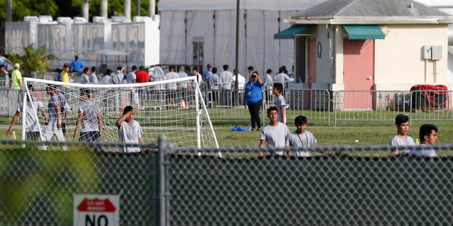 Immigrant children play outside a former Job Corps site that now houses them in Homestead, Fla. It is not known if the children crossed the border as unaccompanied minors or were separated from family members.