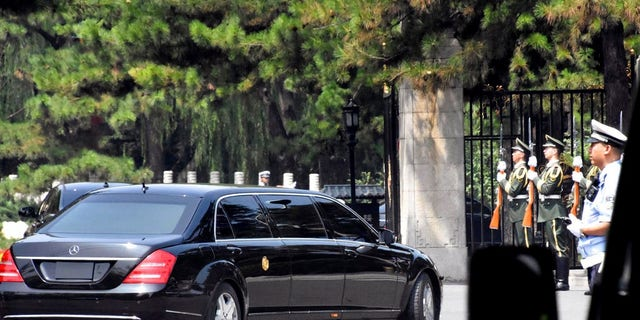 A stretch limousine with a golden emblem similar to one North Korean leader Kim Jong Un has used previously, arrives with motorcycle escorts and guard of honor salute at the Diaoyutai State Guest house in Beijing, China.