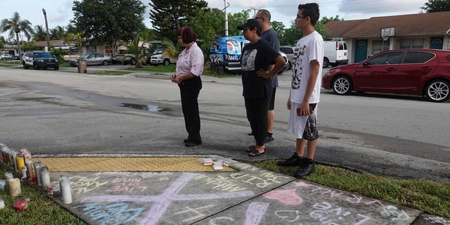 Fans and mourners of rap singer XXXTentacion pause by a memorial, Tuesday, June 19, 2018, outside Riva Motorsports in Deerfield Beach, Fla., where the troubled rapper-singer was killed the day before.