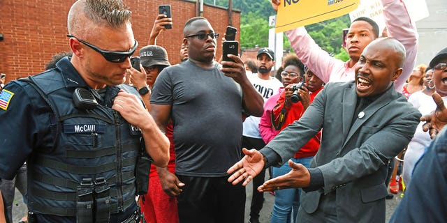 Leonard Hammonds II, of Penn Hills, right, points out that a Turtle Creek Police officer has his hand on his weapon during a rally in East Pittsburgh, Pa., on Wednesday, June 20, 2018, at a protest regarding the shooting death of Antwon Rose by an East Pittsburgh Police officer during a traffic stop the night before.