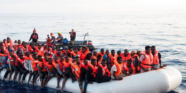 Migrants on a rubber boat are being rescued by the ship operated by the German NGO Mission Lifeline in the Mediterranean Sea in front of the Libyan coast
