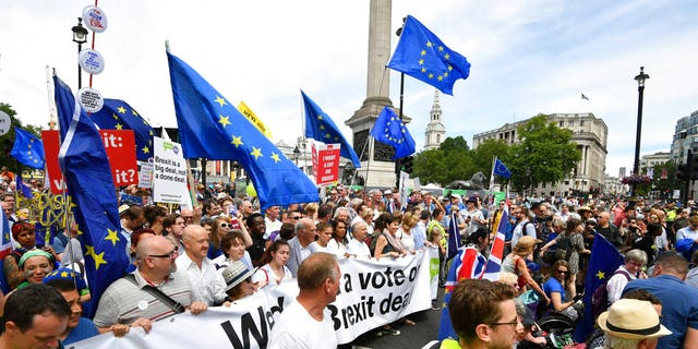 From center carrying banner, British lawmaker Vince Cable, Pro-EU campaigners Gina Miller, Tony Robinson and lawmaker Caroline Lucas join crowds taking part in the People's Vote march for a second EU referendum, at Trafalgar Square in central London