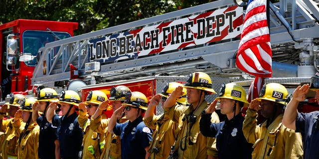 Firefighters salute during a procession for Fire Capt. Dave Rosa who was killed after he was shot responding to an emergency at a senior home in Long Beach, California, on Monday, June 25, 2018.