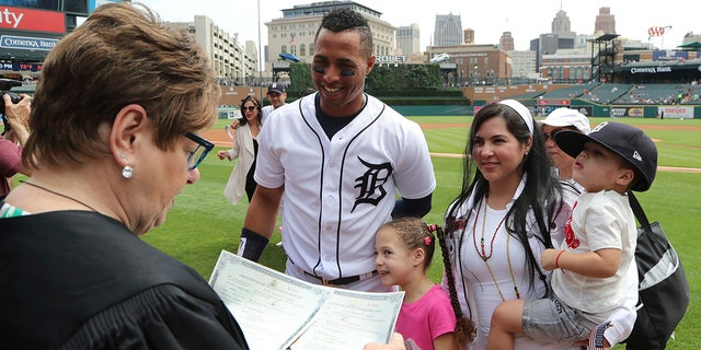 Judge Marianne Battani prepares to give Detroit Tigers center fielder Leonys Martin and his wife Yaimira their naturalization papers after a ceremony before a baseball game, in Detroit.