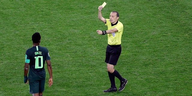 Referee Cuneyt Cakir shows a yellow card to Nigeria's John Obi Mikel during the group D match between Argentina and Nigeria.