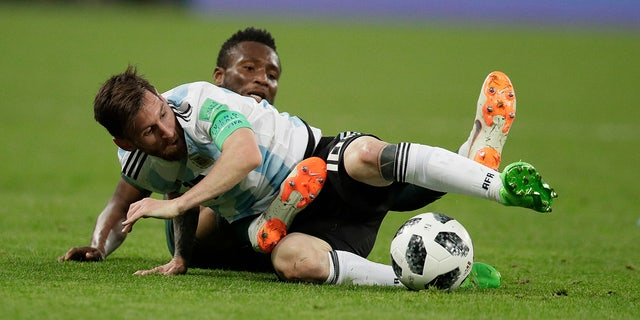 Argentina's Lionel Messi, foreground, and Nigeria's John Obi Mikel compete for the ball during the group D match between Argentina and Nigeria.