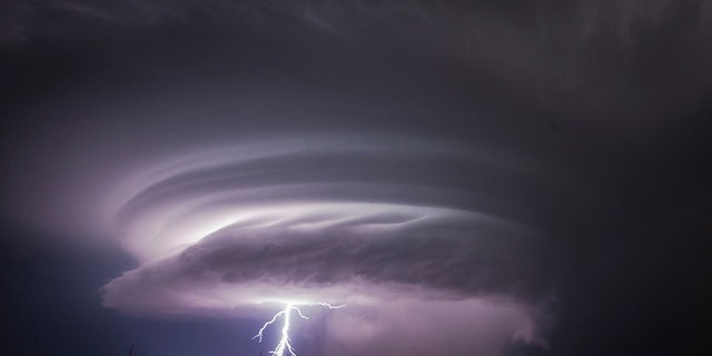 A lightning bolt emerges from a severe thunderstorm just west of Wichita, Kansas.