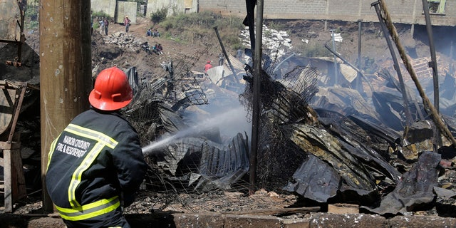 A fire fighter damps down charred debris after a fire swept through a marketplace in Nairobi, Kenya.