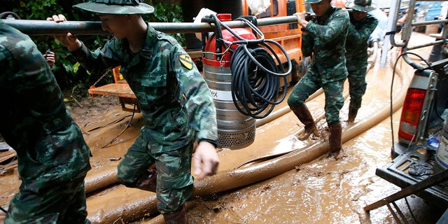 Thai soldiers carry a water pump to drain the water from a cave where 12 boys and their soccer coach have been missing in Mae Sai, Chiang Rai province in northern Thailand.