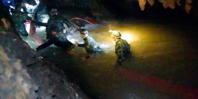 In this handout photo released by Tham Luang Rescue Operation Center, Thai rescue teams walk inside cave complex where 12 boys and their soccer coach went missing, in Mae Sai, Chiang Rai province, in northern Thailand, Monday, July 2