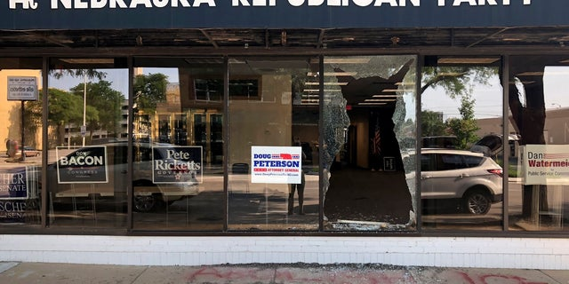 """A broken window greets passers-by outside the Nebraska Republican Party's office in Lincoln, Neb., on Tuesday, July 3, 2018. Vandals threw a brick through the window overnight and scrawled the words """"Abolish ICE"""" on the sidewalk below it."""