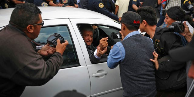 Mexico's President-elect Andres Manuel Lopez Obrador greets a supporter as he leaves the National Palace where he met with Mexico's President Enrique Pena Nieto in Mexico City, Tuesday, July 3, 2018.