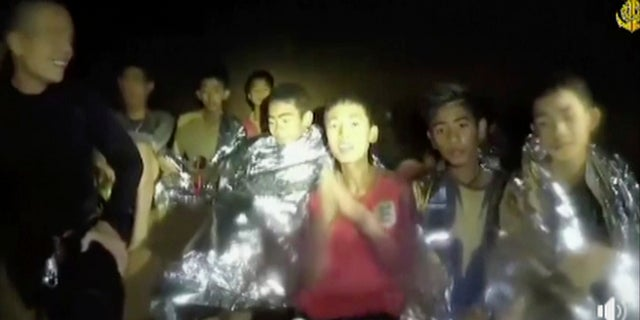 In this July 3, 2018, image taken from video provided by the Thai Navy Seal, Thai boys are with Navy SEALs inside the cave, Mae Sai, northern Thailand.