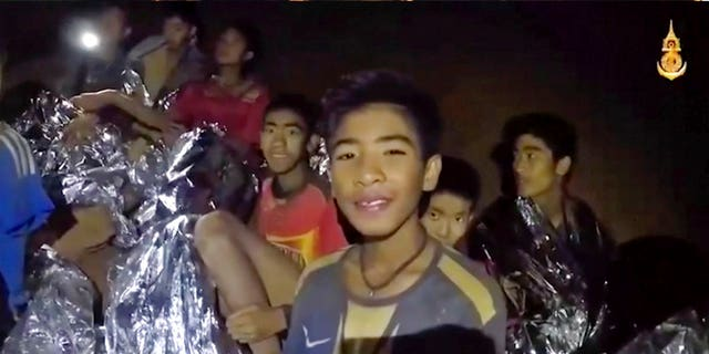 In this July 3, 2018, image taken from video provided by the Royal Thai Navy Facebook Page, Thai boys smile as a Thai Navy SEAL medic helps injured children.