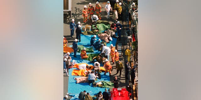 In this March 20, 1995, file photo, the injured of the deadly gas attack are treated by rescuers near Tsukiji subway station in Tokyo.