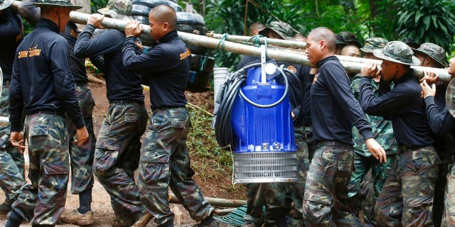 Soldiers carry a pump to help drain the rising flood water in a cave where 12 boys and their soccer coach have been trapped since June 23