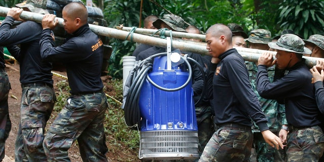 Soldiers carry a pump to help drain the rising flood water in a cave where 12 boys and their soccer coach have been trapped since June 23, in Mae Sai, Chiang Rai province, in northern Thailand Friday, July 6, 2018.