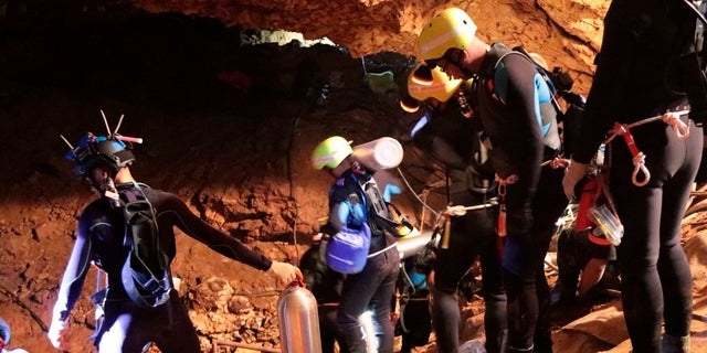 In this undated photo released by Royal Thai Navy on Saturday, July 7, 2018, Thai rescue team members walk inside a cave where 12 boys and their soccer coach have been trapped since June 23.