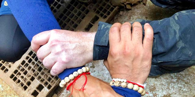 """Thailand Navy SEAL posted on Facebook showing rescuers locking hands with a caption reading: """"We Thai and the international teams join forces to bring the young Wild Boars home."""""""