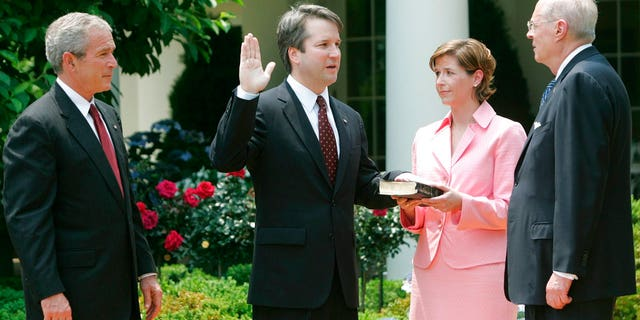 In this June 1, 2006 file photo, from left to right, President Bush, watches the swearing-in of Brett Kavanaugh as Judge for the U.S. Court of Appeals for the District of Columbia by U.S. Supreme Court Associate Justice Anthony M. Kennedy, far right, during a ceremony in the Rose Garden of the White House, in Washington.